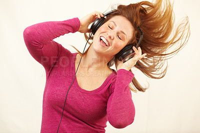 Buy stock photo Cropped shot of a happy young woman dancing while listening to music