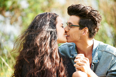 Buy stock photo Cute young couple sitting outside and kissing
