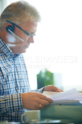 Buy stock photo A senior businessman wearing a headset while going through the financial books in his office