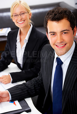 Buy stock photo Portrait of a handsome young man in a business suit, with a beautiful female business colleague in the background.