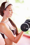 A fit young woman doing bicep curls with a pair of dumbbells