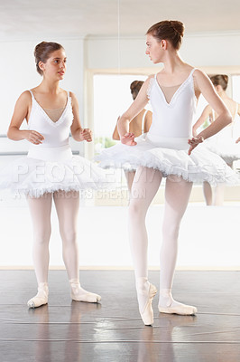 Buy stock photo Full length shot of two ballerinas talking in a studio with a mirror behind them