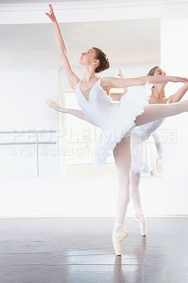 Buy stock photo Full length shot of a ballerina practicing in a studio