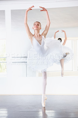 Buy stock photo Shot of a ballerina rehearsing in a studio with a mirror behind her