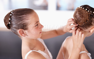 Buy stock photo Shot of young ballerina helping adjust her friend's bun before rehearsal