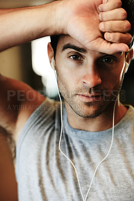 Buy stock photo Portrait of a man wearing earphone and standing with wrist rested against his forehead