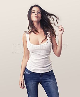 Buy stock photo Gorgeous young brunette playing with her long hair and giving you a slight smile