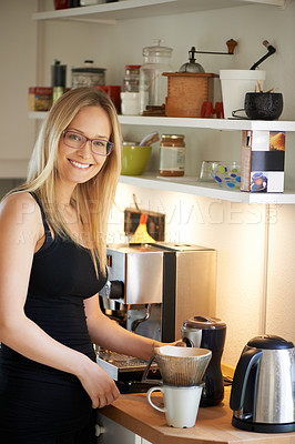 Buy stock photo Attractive young woman making coffee at her kitchen counter