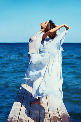 Buy stock photo A beautiful young woman with her arms outstretched on the pier