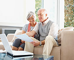 Senior couple with laptop reading a document at their house