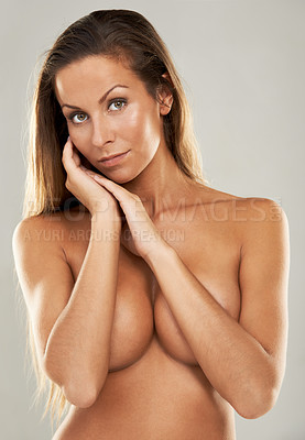 Buy stock photo Shot of a gorgeous young woman covering her breasts against a gray background