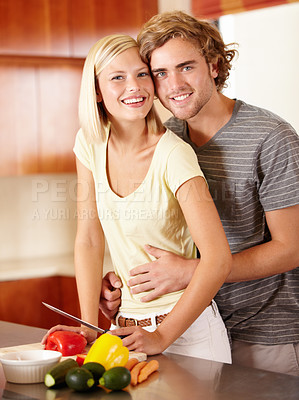 Buy stock photo Portrait of a happy young couple standing in the kitchen