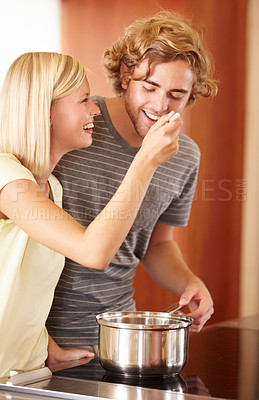 Buy stock photo A young man tasting his girlfriend's food in the kitchen