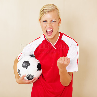 Buy stock photo Shot of a young woman dressed in a soccer uniform celebrating and holding a soccer ball