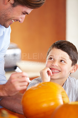 Buy stock photo A father and son carving a pumpkin in the kitchen for halloween