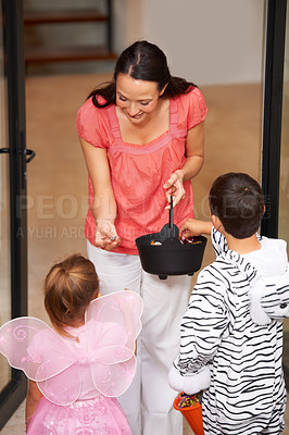 Buy stock photo Cropped shot of a woman handing out candy to two little trick-or-treaters