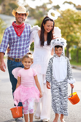 Buy stock photo Shot of a family walking down the road in their Halloween costumes