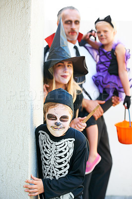Buy stock photo A cute family dressed up for Hallowe'en sneaking up to you to scare you!