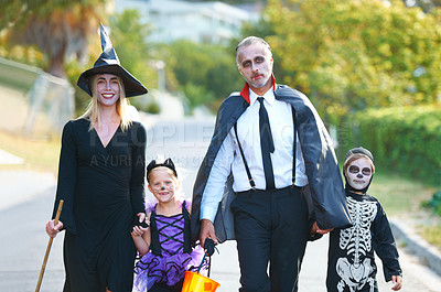 Buy stock photo A cute family dressed up for Hallowe'en walking down their street