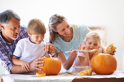 Buy stock photo A family of four hollowing out pumpkins for halloween in the kitchen