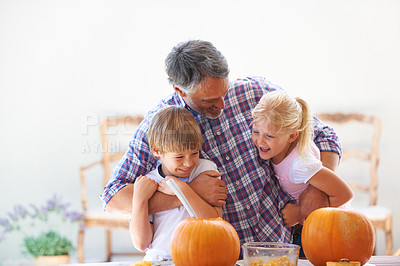 Buy stock photo A father embracing his son and daughter while hollowing out pumpkins for halloween