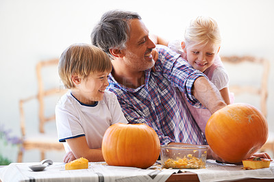 Buy stock photo A father, his son and his daughter hollowing out pumpkins for halloween