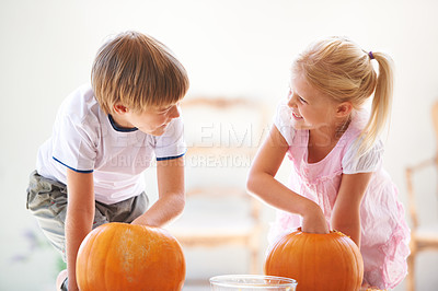 Buy stock photo A little boy and girl hollowing out their jack-o-lantern