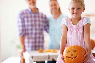 Buy stock photo Portrait of a little girl holding her jack-o-lantern with her parents blurred in the background