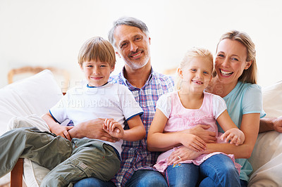 Buy stock photo Portrait of a family of four sitting on the sofa