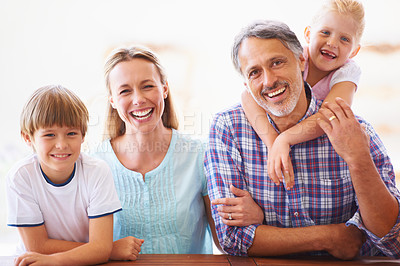 Buy stock photo Portrait of a family of four sitting at home