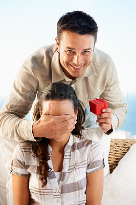 Buy stock photo A young man holding a ring box with his hand on his girlfriend's eyes