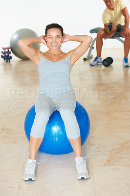 Buy stock photo A young woman doing sit-ups on a yoga ball