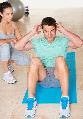 Buy stock photo A fitness instructor showing a young man how to do an exercise