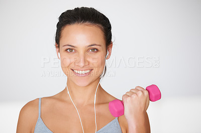 Buy stock photo Portrait of a young woman working out with weights while listening to music