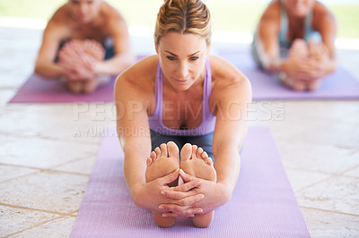 Buy stock photo Young yoga instructor leading a class