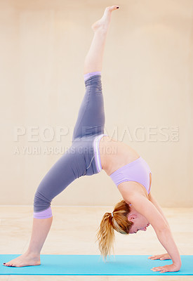 Buy stock photo Supple sportswoman in a yoga position while doing yoga by herself