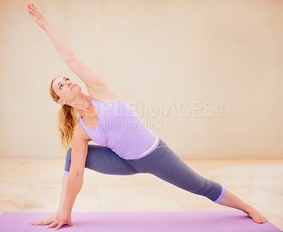 Buy stock photo Supple woman in a yoga position while doing yoga by herself