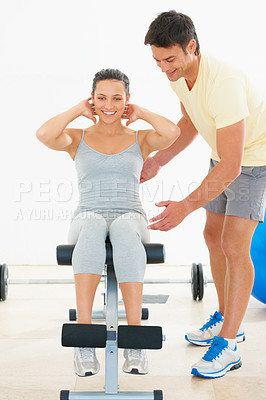 Buy stock photo A fitness instructor showing a young woman how to do an exercise