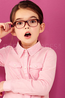 Buy stock photo A little girl with expression of surprise holding the edge of her spectacles against a pink background