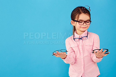Buy stock photo A little girl standing with spectacles in her hand, on her head, and around her neck against a blue background