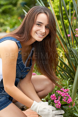 Buy stock photo Portrait of a beautiful young woman planting some new flowers in her garden