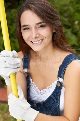 Buy stock photo Portrait of an attractive young woman holding a rake