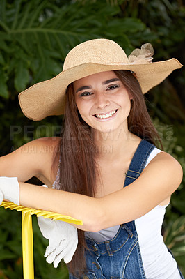 Buy stock photo Portrait of an attractive young woman leaning on a rake