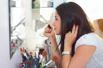 Buy stock photo Cropped shot of an attractive young woman applying makeup in the bathroom