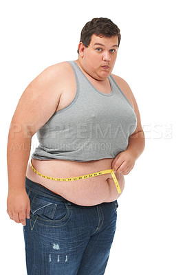 Buy stock photo Portrait of an obese young man pulling in his stomach while measuring his waist with a measuring tape