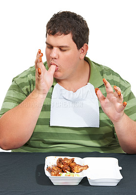 Buy stock photo An obese young man wearing a bib and siting at a table with a container of saucy chicken wings and licking his sauce covered fingers