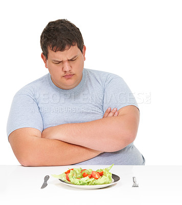 Buy stock photo An obese young man sitting with arms folded at a table with a plate of salad in front of him