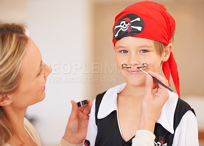 Buy stock photo Portrait of a smiling boy standing infront of his mother who is painting a mustache on his face