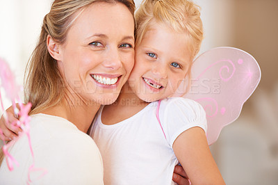 Buy stock photo A smiling mother embracing her daughter who is dressed up as a fairy