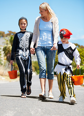 Buy stock photo Children in costume going treat or treating with their mom